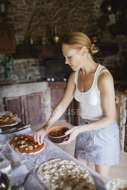Side view of woman preparing homemade pizzas — Stock Photo