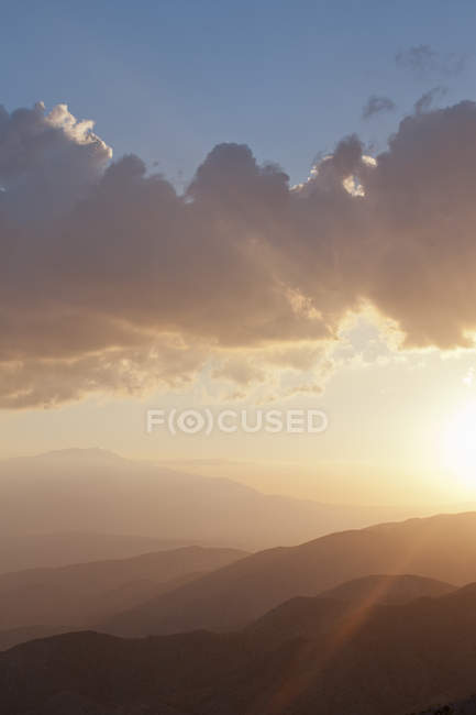 View of silhouetted mountains in cloudy sunset sky — Stock Photo
