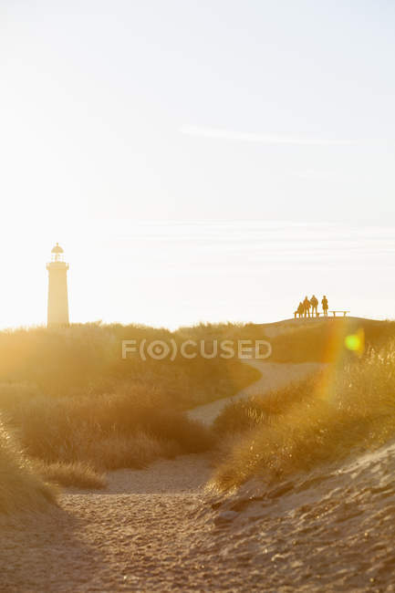Silhouetted group of people and lighthouse in sunset light — Stock Photo