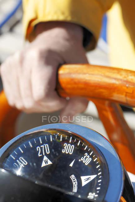 Крупным планом капитан держит в руках деревянный руль — стоковое фото