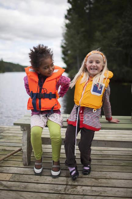 Дві дівчинки, носити жилети, зосередитися на передньому плані — стокове фото