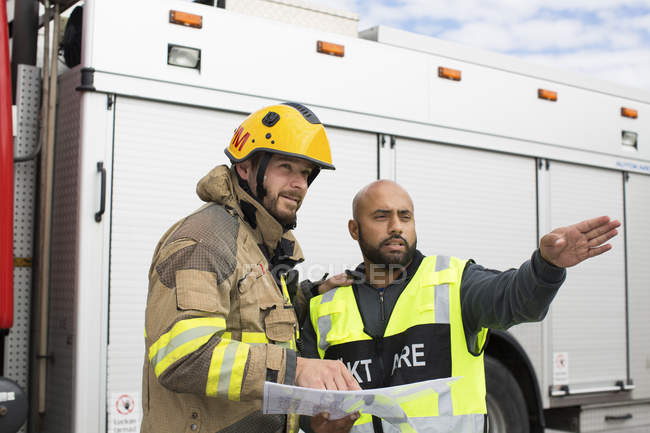 Security guard and firefighter discussing plan — Stock Photo