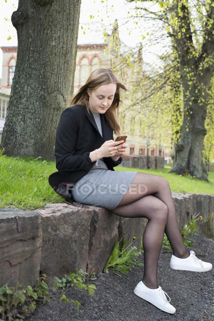 Giovane donna texting nel parco, fuoco selettivo — Foto stock