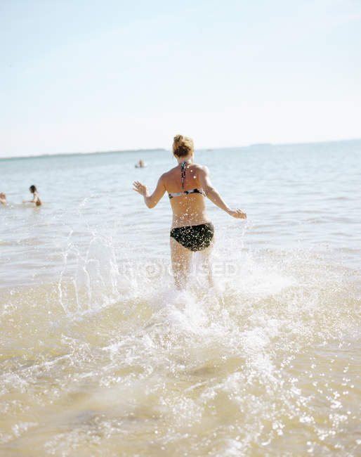 Rear view of young woman running into water — Stock Photo