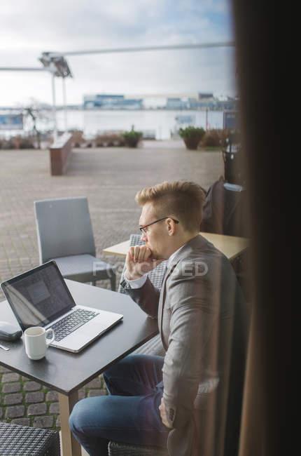 Homem de negócios usando o laptop no café, foco diferencial — Fotografia de Stock