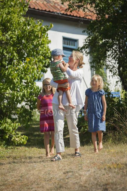 Mãe com filhas e filho no quintal, foque em primeiro plano — Fotografia de Stock