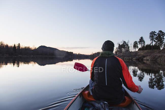 Вид сзади человека каноэ на закате — стоковое фото