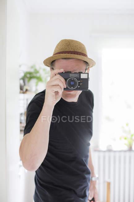 Солом'яному капелюсі дивлячись через камеру людини — стокове фото