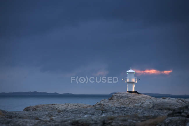 Illuminated lighthouse on rocks at dusk with cloudy sky — Stock Photo