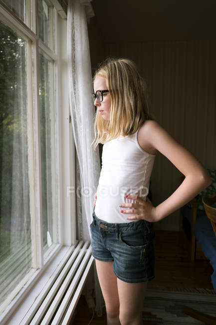 Girl looking though window, selective focus — Photo de stock