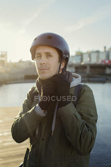 Outdoor portrait of mid adult man tying helmet strap — Stock Photo