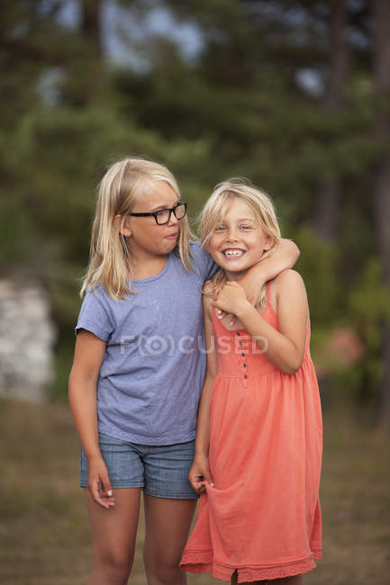 Girl in spectacles embracing sister, focus on foreground — Stock Photo