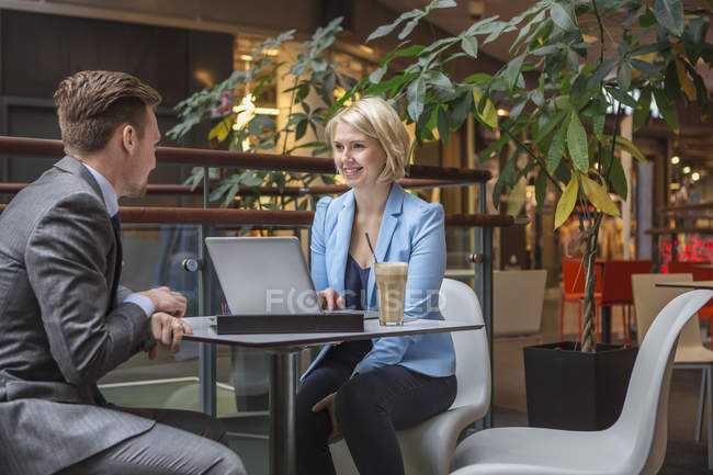 Businessman and businesswoman in cafe, focus on foreground — Stock Photo