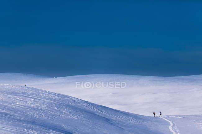 Bulletins d'enneigement des collines recouvertes des randonneurs lointains — Photo de stock