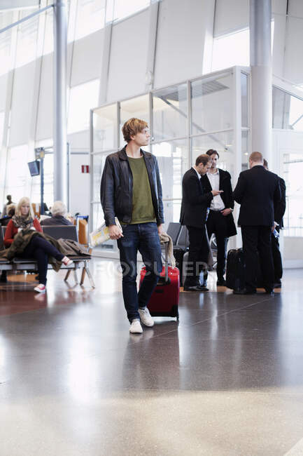 Mid adult man with suitcase looking aside at airport — Stock Photo