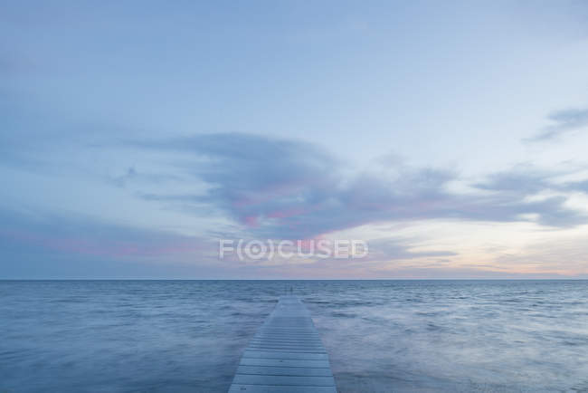 Front view of seascape with pier at sunset — Stock Photo