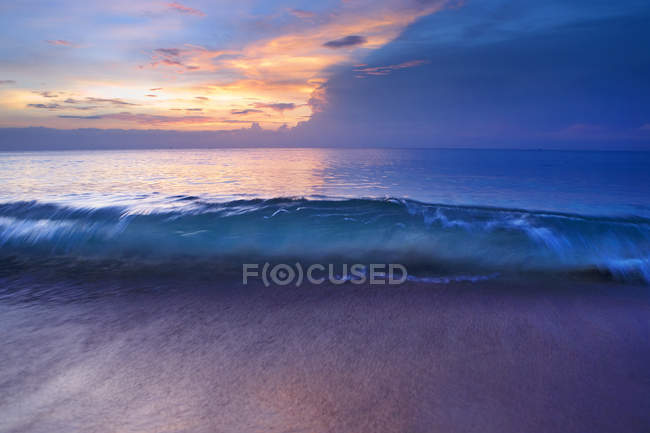 Blurred motion shot of surf wave at sunset — Stock Photo