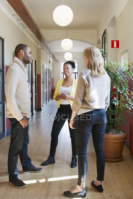 Colleagues talking in corridor, focus on foreground — Stock Photo
