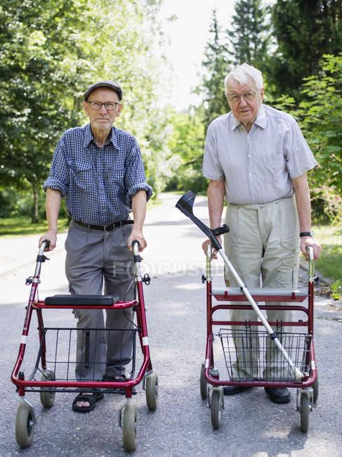 Two senior men with walking frames looking at camera — Stock Photo