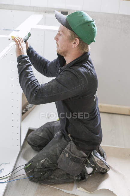 Carpenter in protective workwear installing furniture — Stock Photo