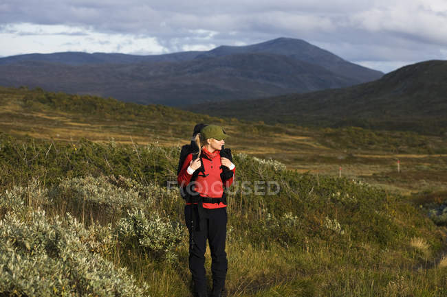 Woman hiking among hills, focus on foreground — Stock Photo