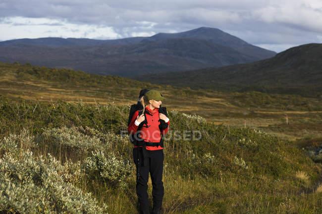 Donna escursionismo tra le colline, concentrarsi sul primo piano — Foto stock