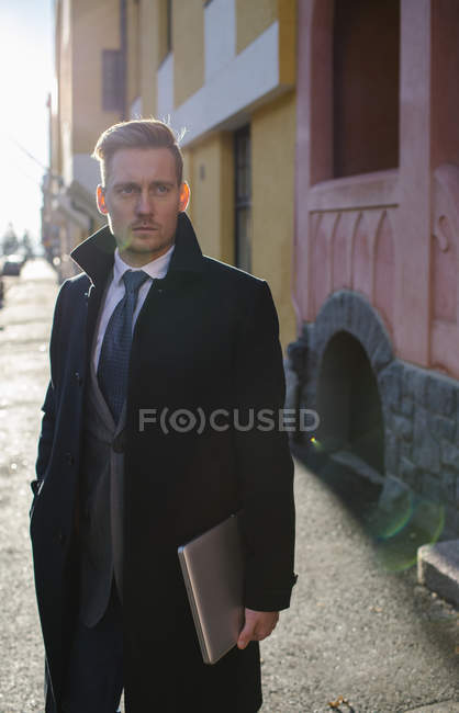 Businessman with laptop in sunlit street, differential focus — Stock Photo