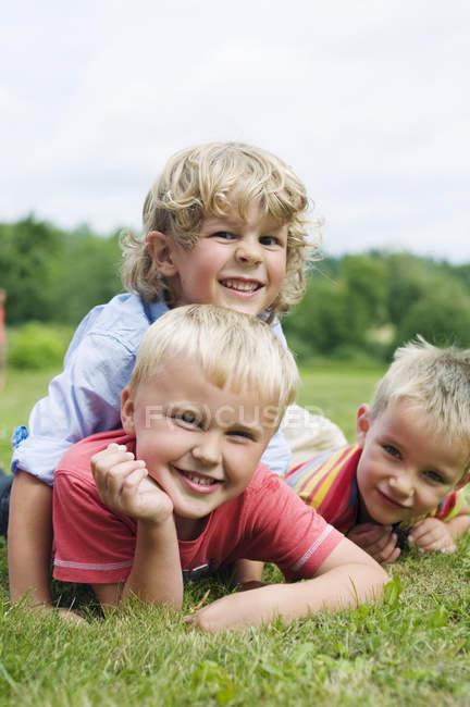 Трьох хлопчиків, які лежать на траві, зосередитися на передньому плані — стокове фото