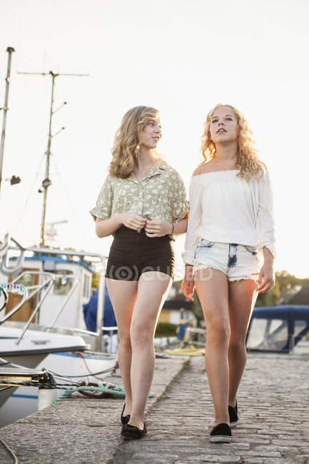 Two teenage girls walking at marina bay, focus on foreground — Stock Photo