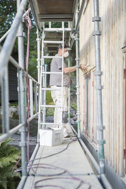 Man on scaffolding fixing siding on house — Stock Photo