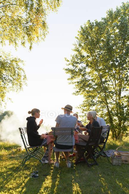 Семья обедает на заднем дворе на закате — стоковое фото