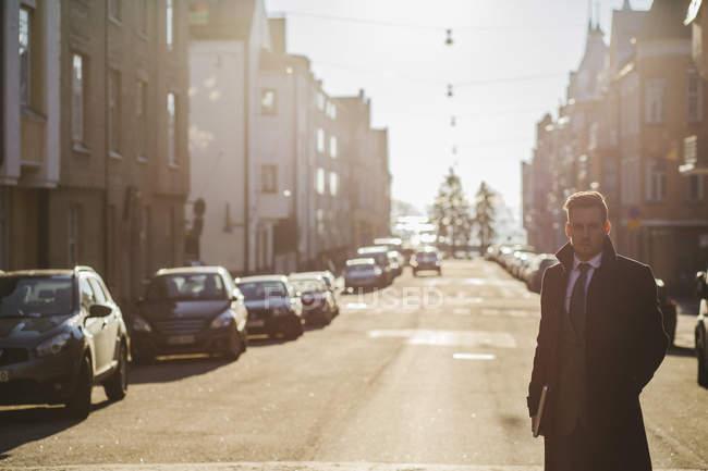Uomo d'affari in strada illuminata dal sole, prospettiva in diminuzione — Foto stock