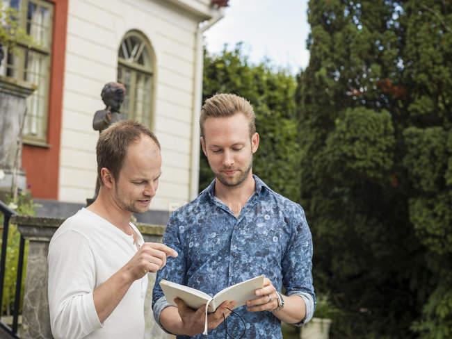 Two men reading book, selective focus — Stock Photo