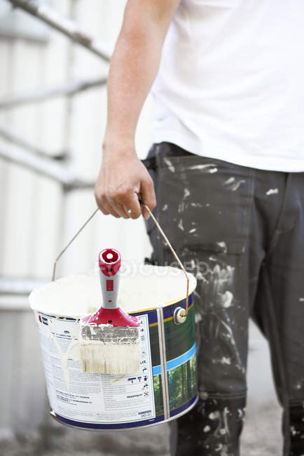 Man carrying bucket of white paint with brush — Stock Photo