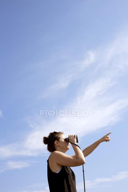 Низький кут зору жінки, дивлячись через бінокль — стокове фото