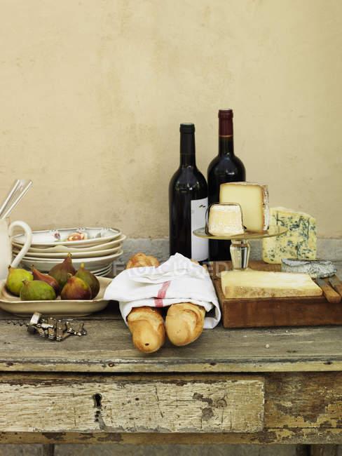 Fatias de queijo, vinho e pão na mesa — Fotografia de Stock