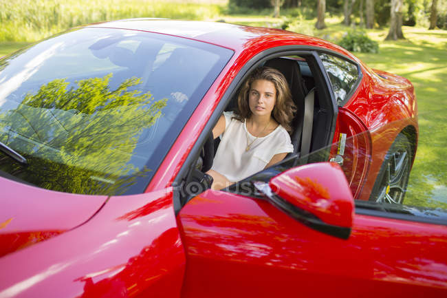 Ragazza adolescente seduta in auto rossa — Foto stock