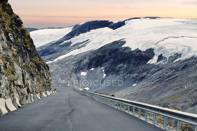 Vista giù la strada che conduce lungo la montagna innevata — Foto stock