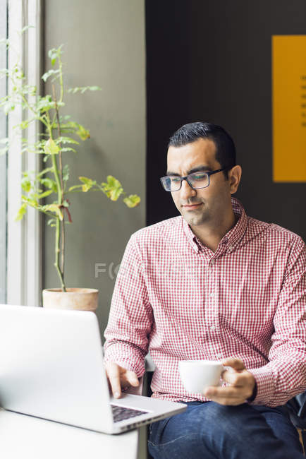 Man using laptop and holding cup while sitting in cafe — Stock Photo