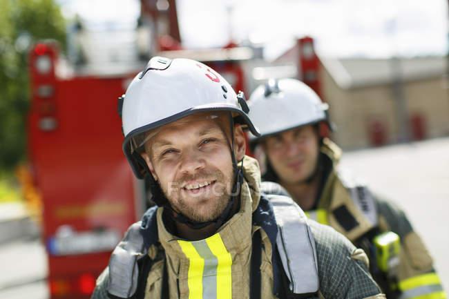 Два пожежних з пожежна машина у фоновому режимі — стокове фото