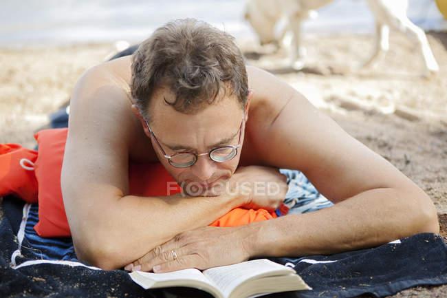 Портрет людина читання на пляжі, зосередити увагу на передньому плані — стокове фото