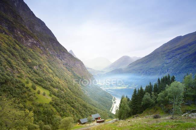 Petites maisons de montagnes verdoyantes avec des nuages bas — Photo de stock