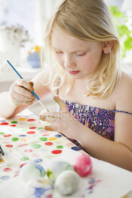 Girl painting easter egg, differential focus — Stock Photo