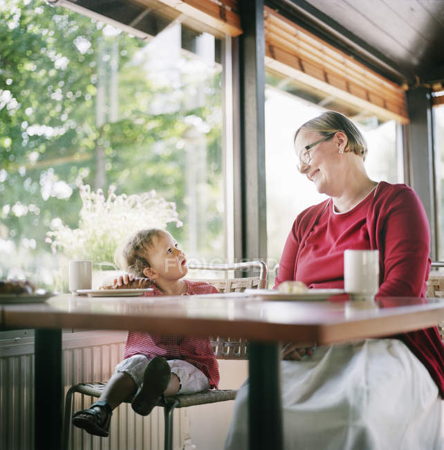Grandmother and granddaughter relaxing in cafe, focus on foreground — Stock Photo
