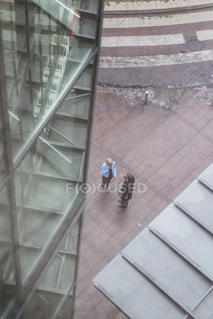 Blick aus der Vogelperspektive auf zwei Geschäftsleute, die neben einem Bürogebäude stehen — Stockfoto