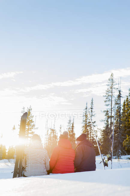 Father and daughters in snowy landscape with skiies, rear view — Stock Photo