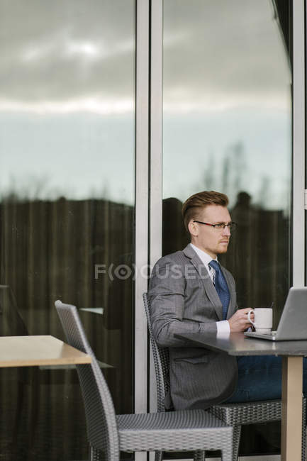 Businessman using laptop at cafe table, differential focus — Stock Photo
