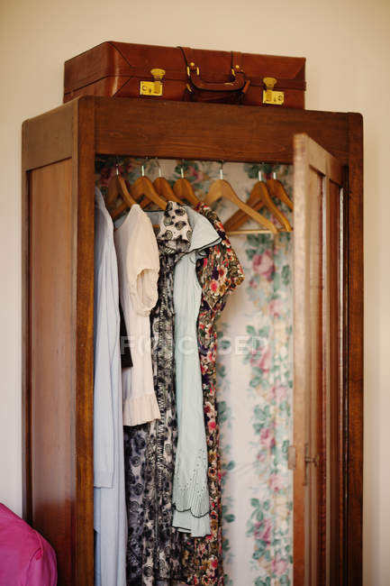 Clothes hanging in open wooden wardrobe — Stock Photo