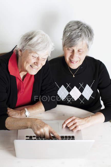 Dos mujeres mayores usando el ordenador portátil y sonriendo - foto de stock