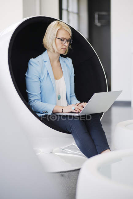 Woman using laptop in ball chair, differential focus — Stock Photo